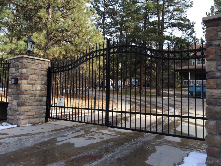 automated decorative iron gate with stone pillars