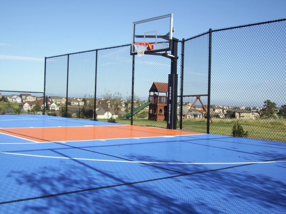 tall black chain link fence around sports park and basketball goal