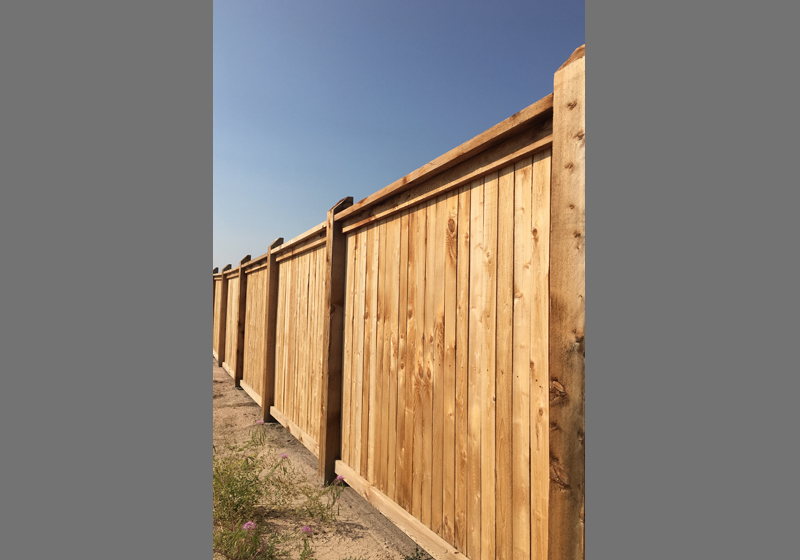 tall wood fence with sloped top posts land management HOA