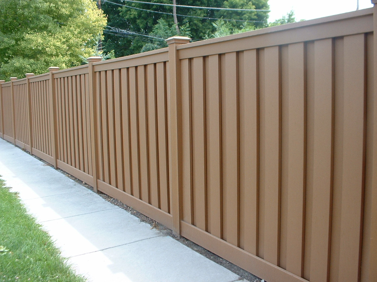 tall brown trex fence near sidewalk HOA