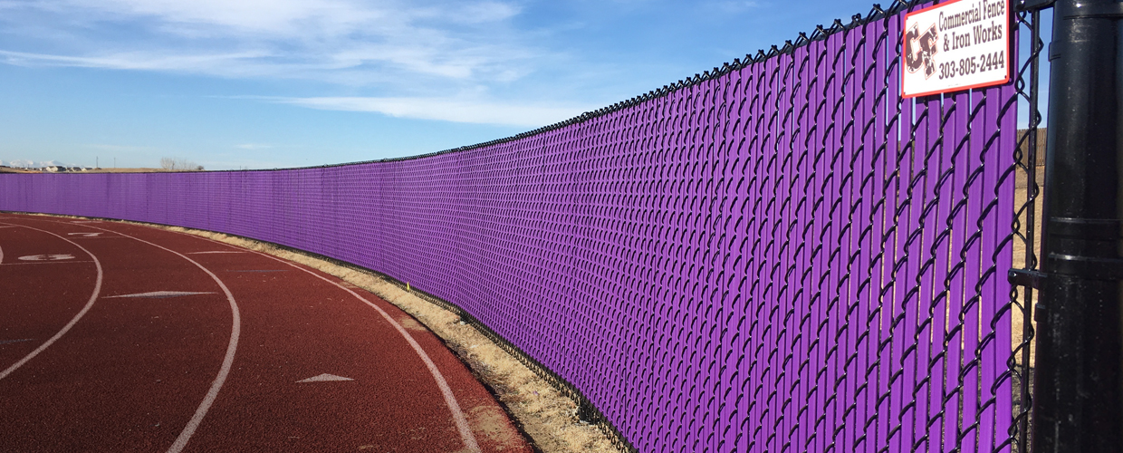 purple chain link fence around running track